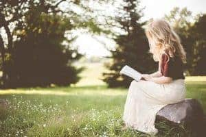 woman sitting on a rock reading Bible