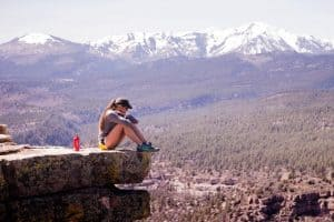 woman sitting on a rock over looking a canyon