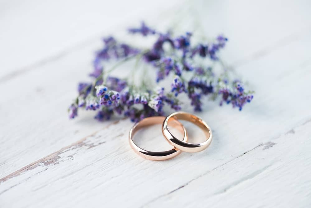 wedding rings on a whitewashed board with purple flowers/how to love your husband when marriage is hard
